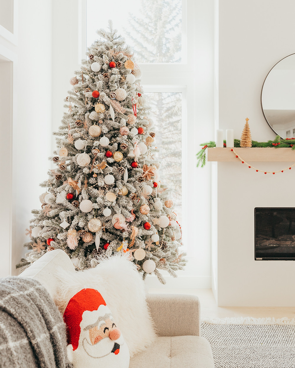 A giant flocked christmas tree decorated with modern blush and red christmas holiday ornaments in a minimal Scandinavian style sits next to a large window in a bright white modern living room with a linear fireplace and. a mantel decorated for the holidays.