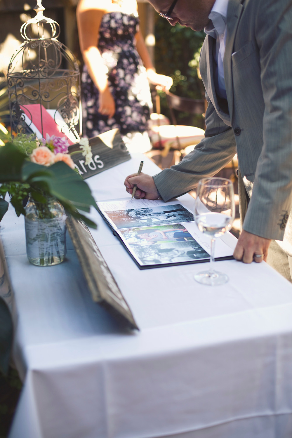 A guest book being signed on a table next to a vase of flowers at a rustic iItalian Inspired wedding.