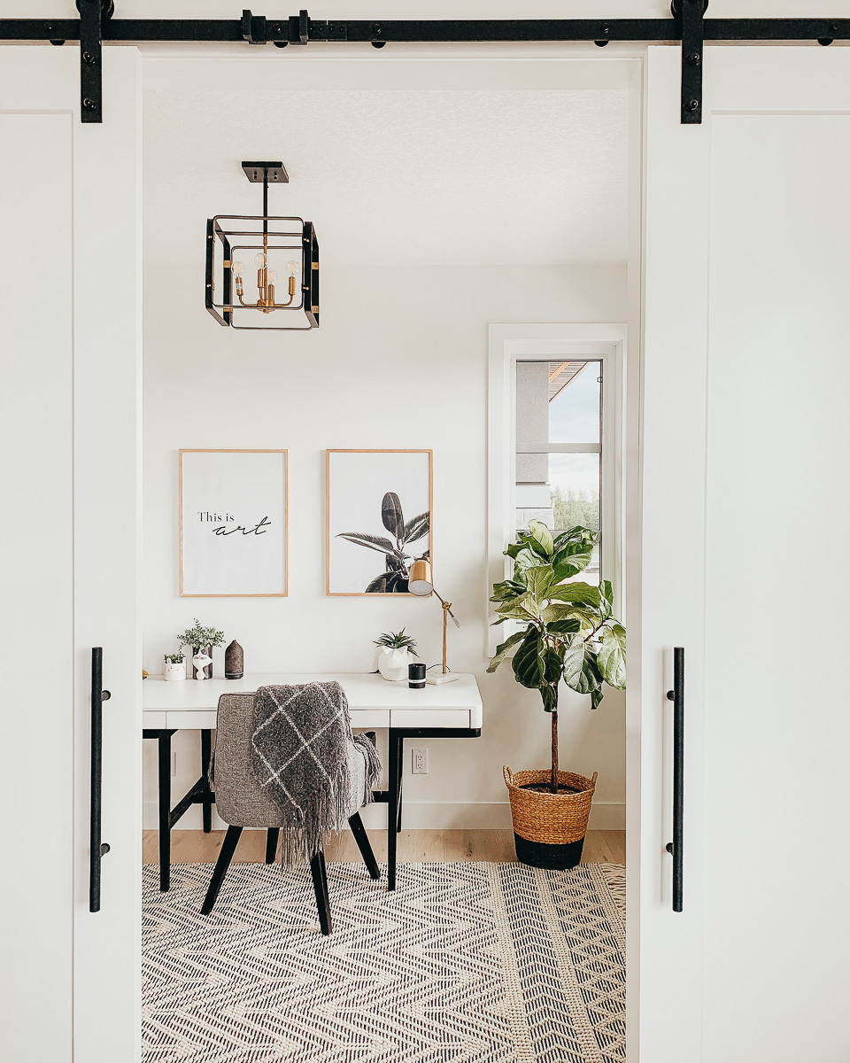 An office with a modern white desk and grey chair on a wool boho rug next to a fiddle leaf fig in a basket below two framed prints.