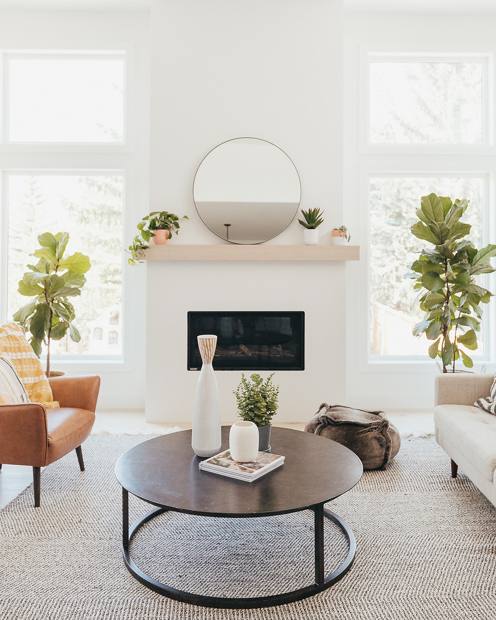 White walls natural light wood mantle with round mirror and three plants on mantle ledge fiddle leaf fig in baskets leather armchair round wood coffee table with magazines and vase and plant cream sofa with faux fur pouf on floor