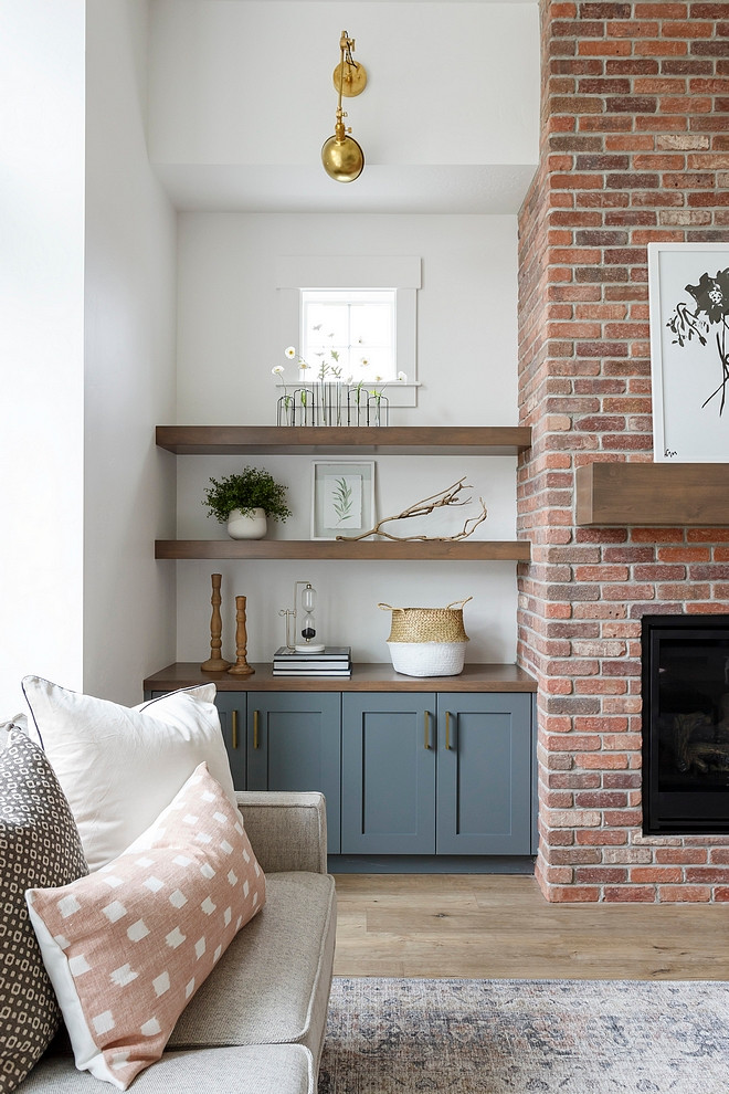 exposed brick fireplace with wood mantle blue cabinets with open wooden shelves brass wall long arm sconce small picture window vase with daisies framed print throw pillows on beige couch natural light hardwood floors