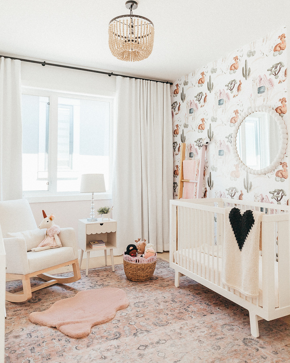 A boho modern baby girls nursery with llama and cactus wallpaper, a blush pink rug, a white joya monte designs rocking chair, a beaded light pendant, a white crib and a scalloped pink wall behind white drapery.
