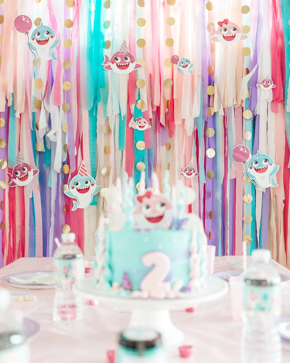 A two year old little girl Baby Shark birthday party with a streamer backdrop, baby shark cake, baby shark cookies, floating balloons, home-made play dough party favours all done in pink teal purple and white party decor #partyideas #babysharkparty #babysharktablesettings #babysharkpartydecorations