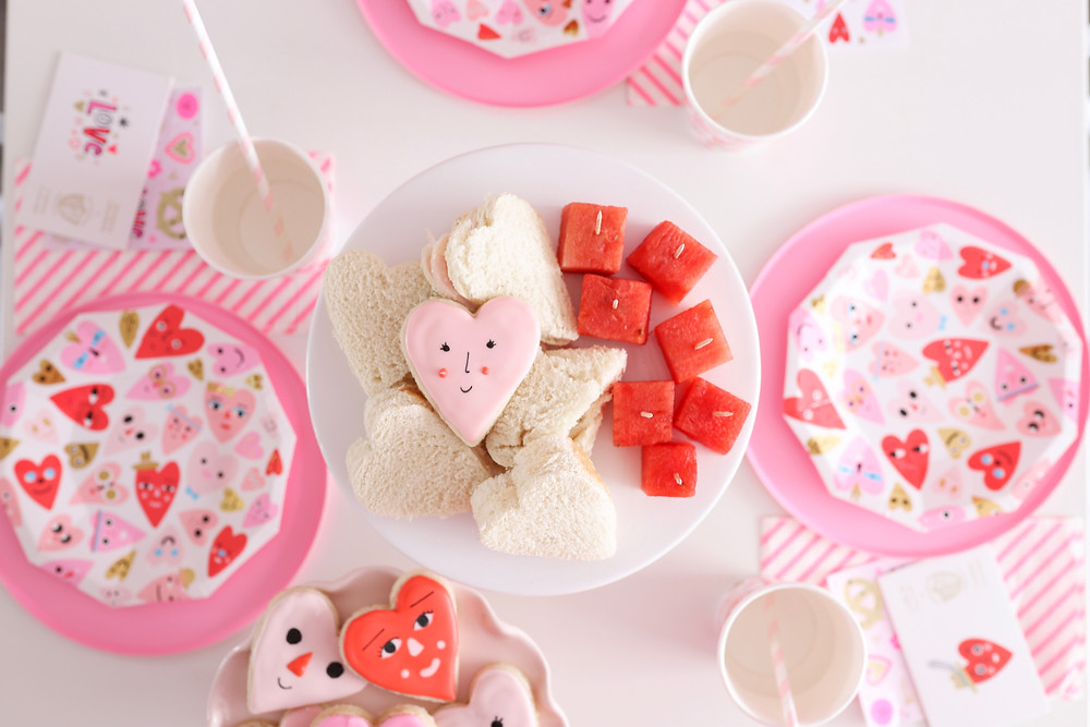 A table set for a Valentine's Day party with treats and pretty heart plates.