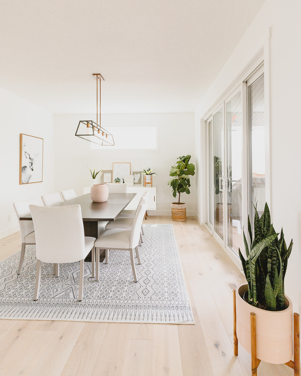 A modern dining room with a white aztec area rug and a dark brown dining table with white chairs in front of a midcentury modern console table.