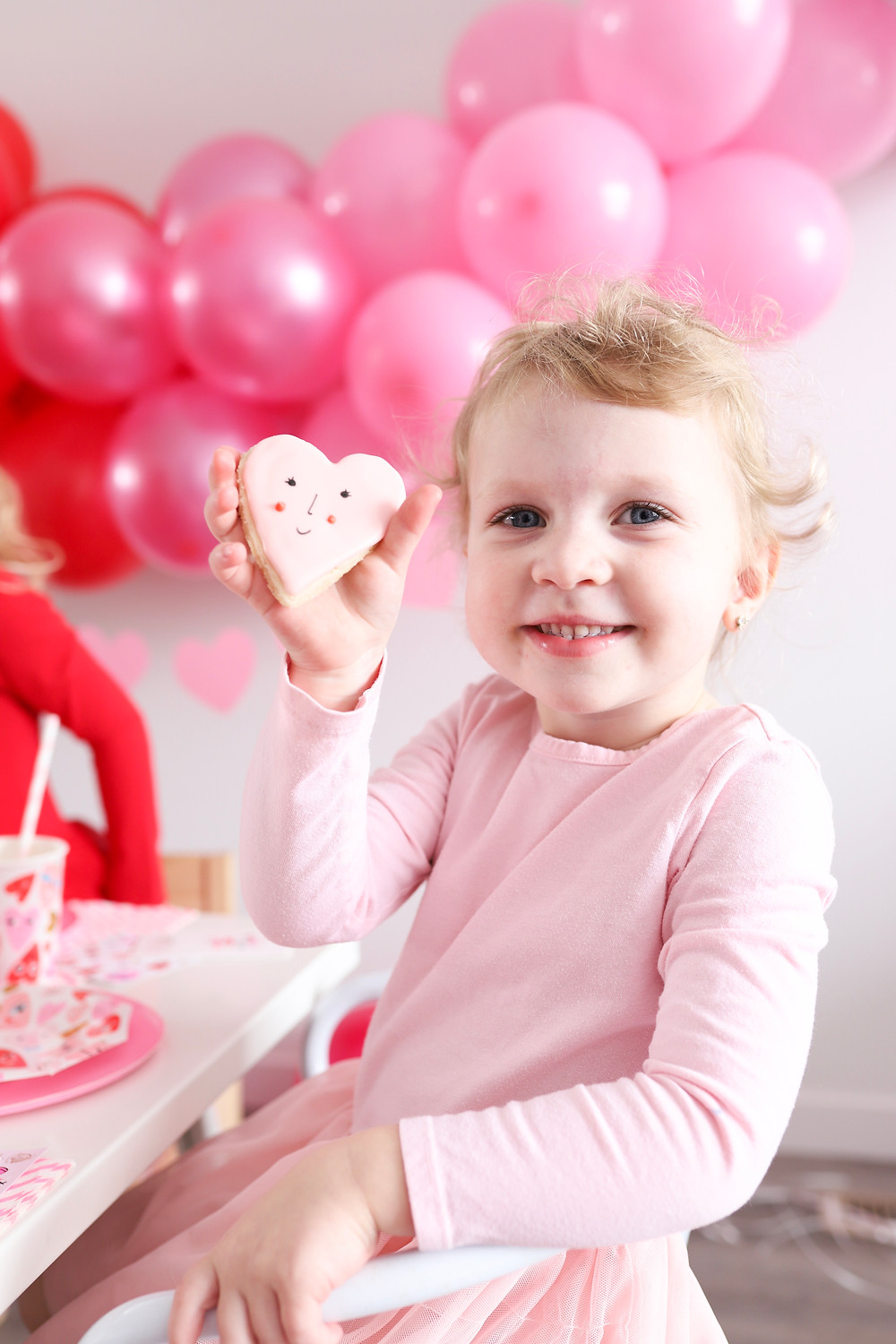 A little girl smiling at the camera holding a Valentine's Day cookie.