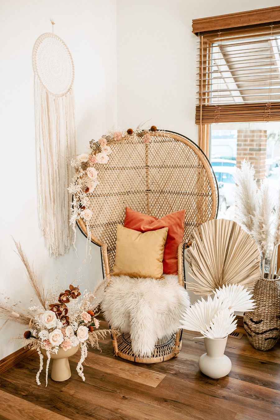 A boho vintage rattan wicker chair at a baby shower is decorated with vintage inspired flowers, pampas grasses, lace and fur throws.