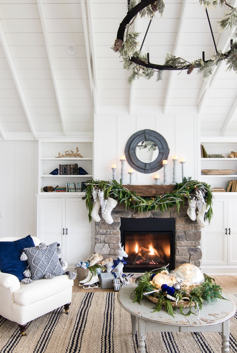 A white Christmas holiday fireplace with a mantel decorated with greenery, bottle brush trees and stockings for a stylish and modern look.