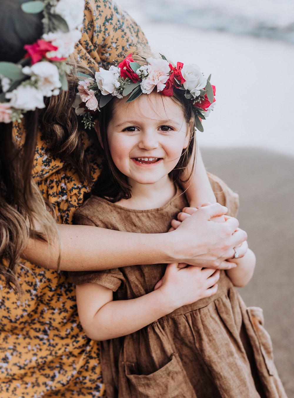A little girl is looking at the camera smiling with a flower crown in her hair.