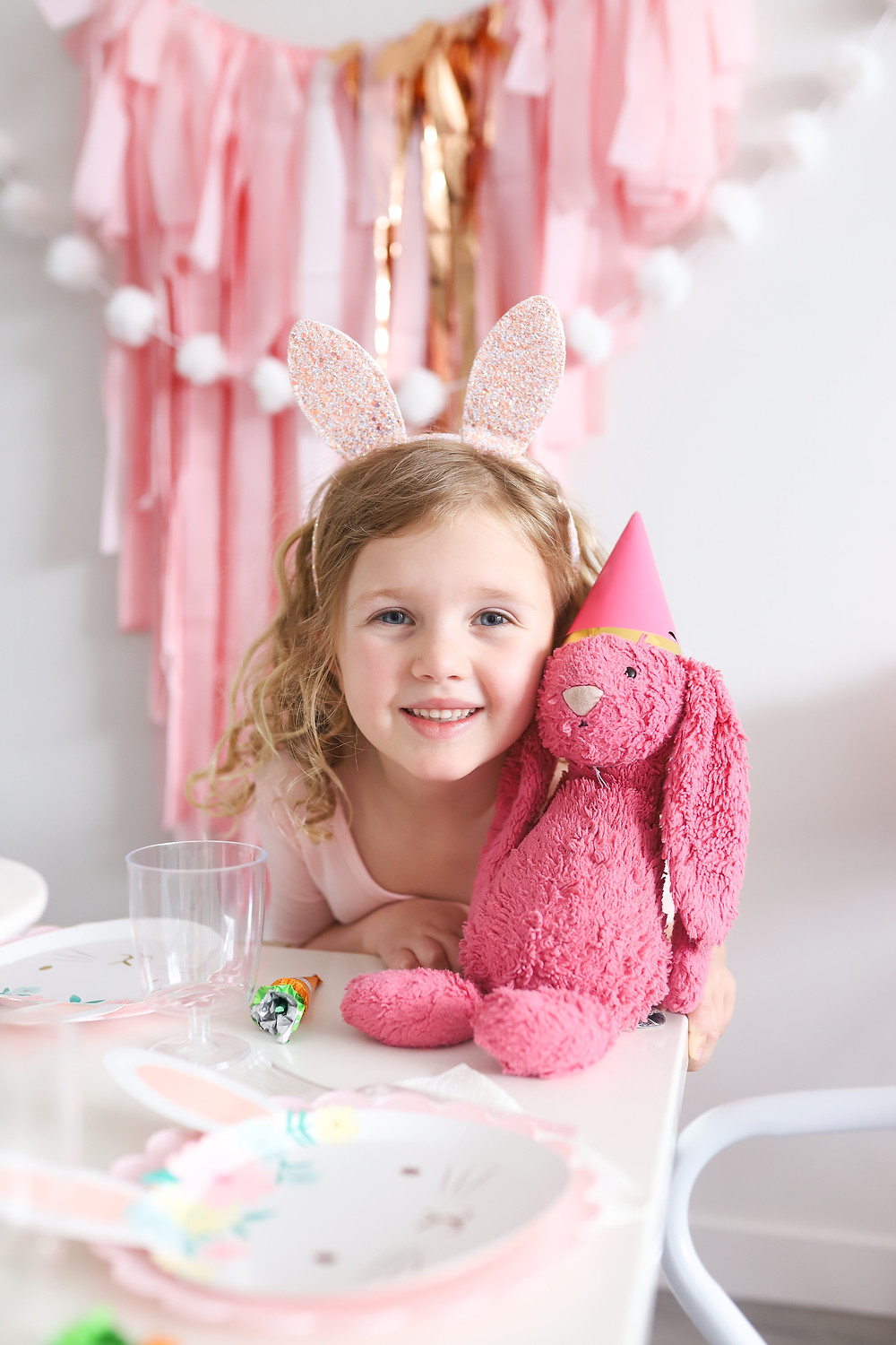 A little girl with curly blonde hair wearing bunny ears sitting at a party table with her pink stuffed bunny who is wearing a party hat.
