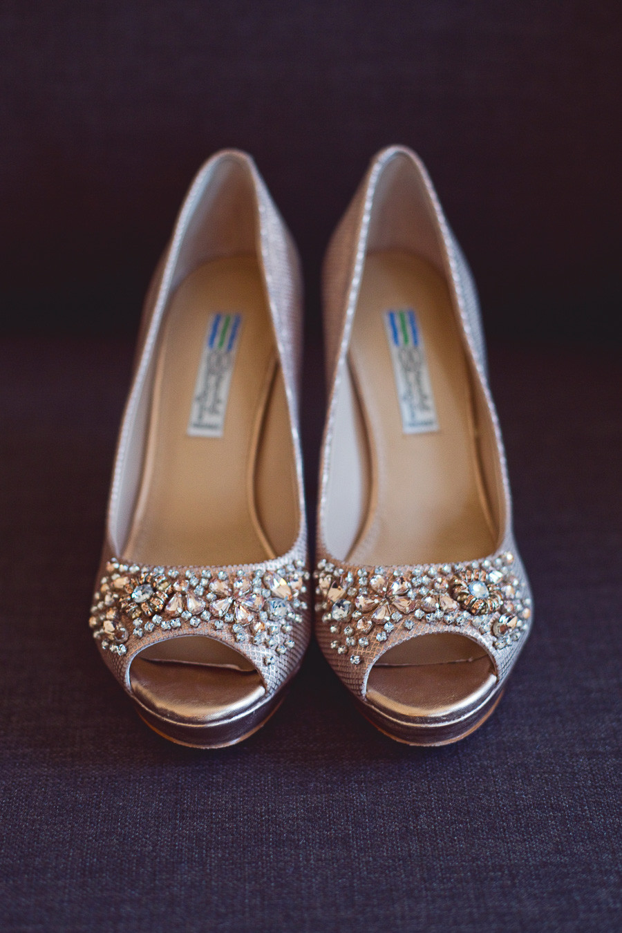 A pair of rose gold crystal wedding shoes for a bride.