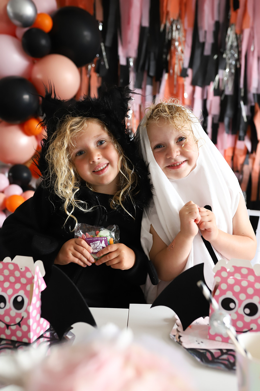 Two little girls dressed up for Halloween in a black cat costume and white ghost costume eating candied treats from their pink party bags, behind a wall filled with pink orange and black balloons and streamers.