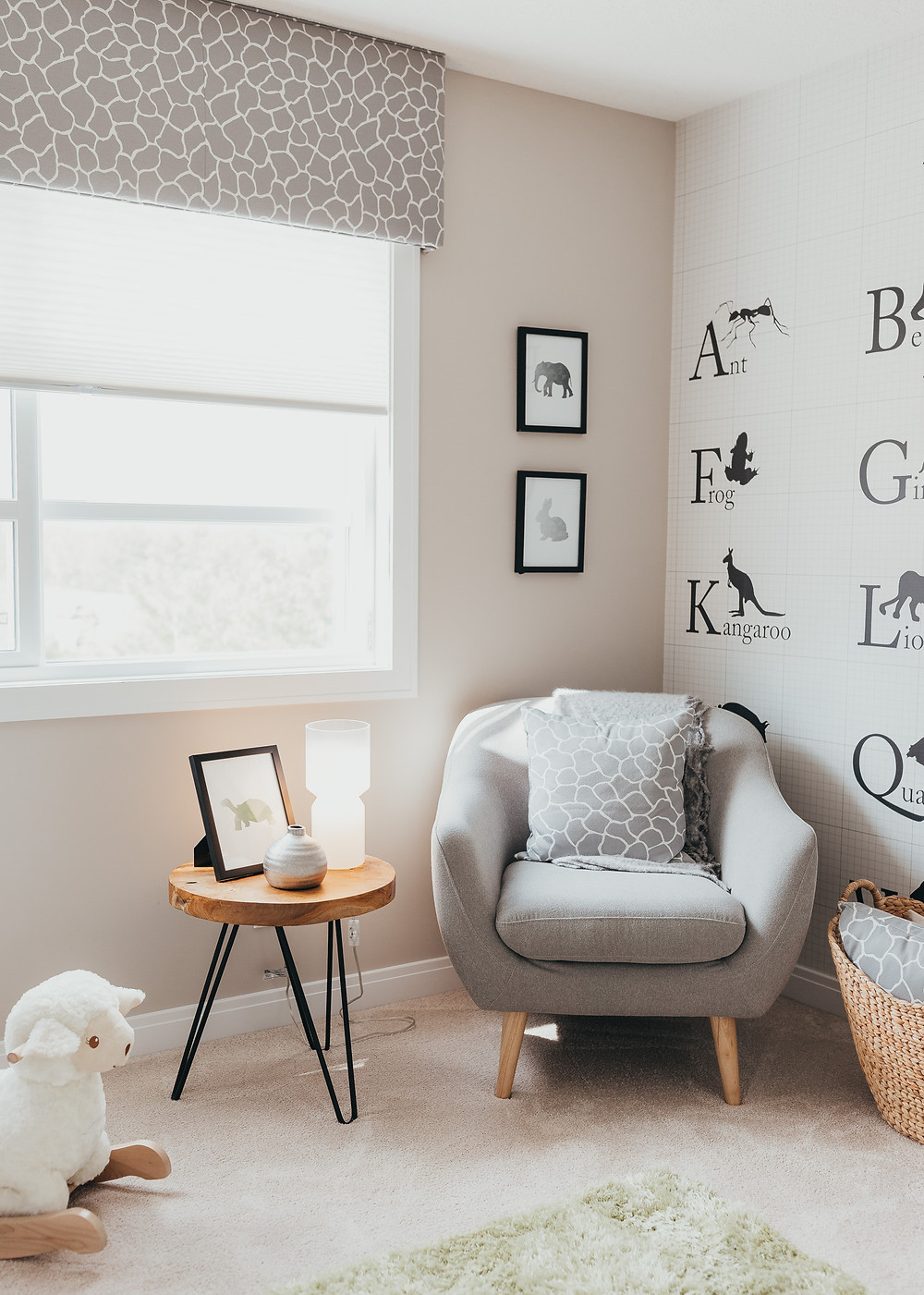 A baby nursery decorated with alphabet wallpaper on the wall.