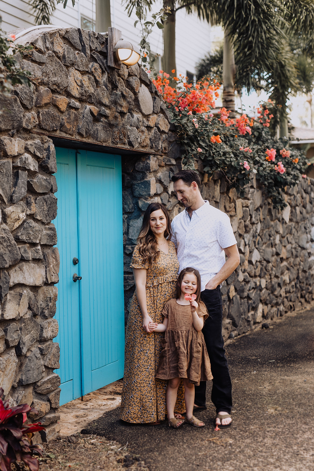 Family standing in front of a blue door in Hawaii