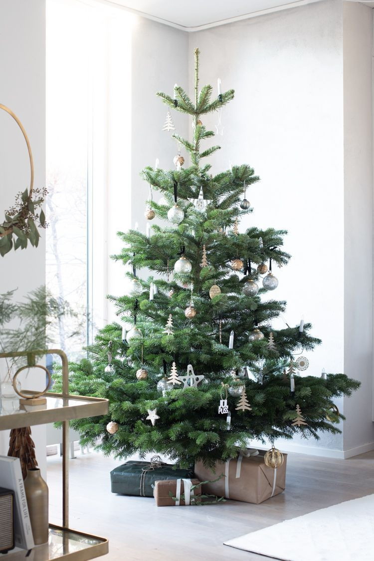 A modern Scandinavian Christmas tree decorated with minimal ornaments with simple gifts wrapped in brown paper sitting below the tree.