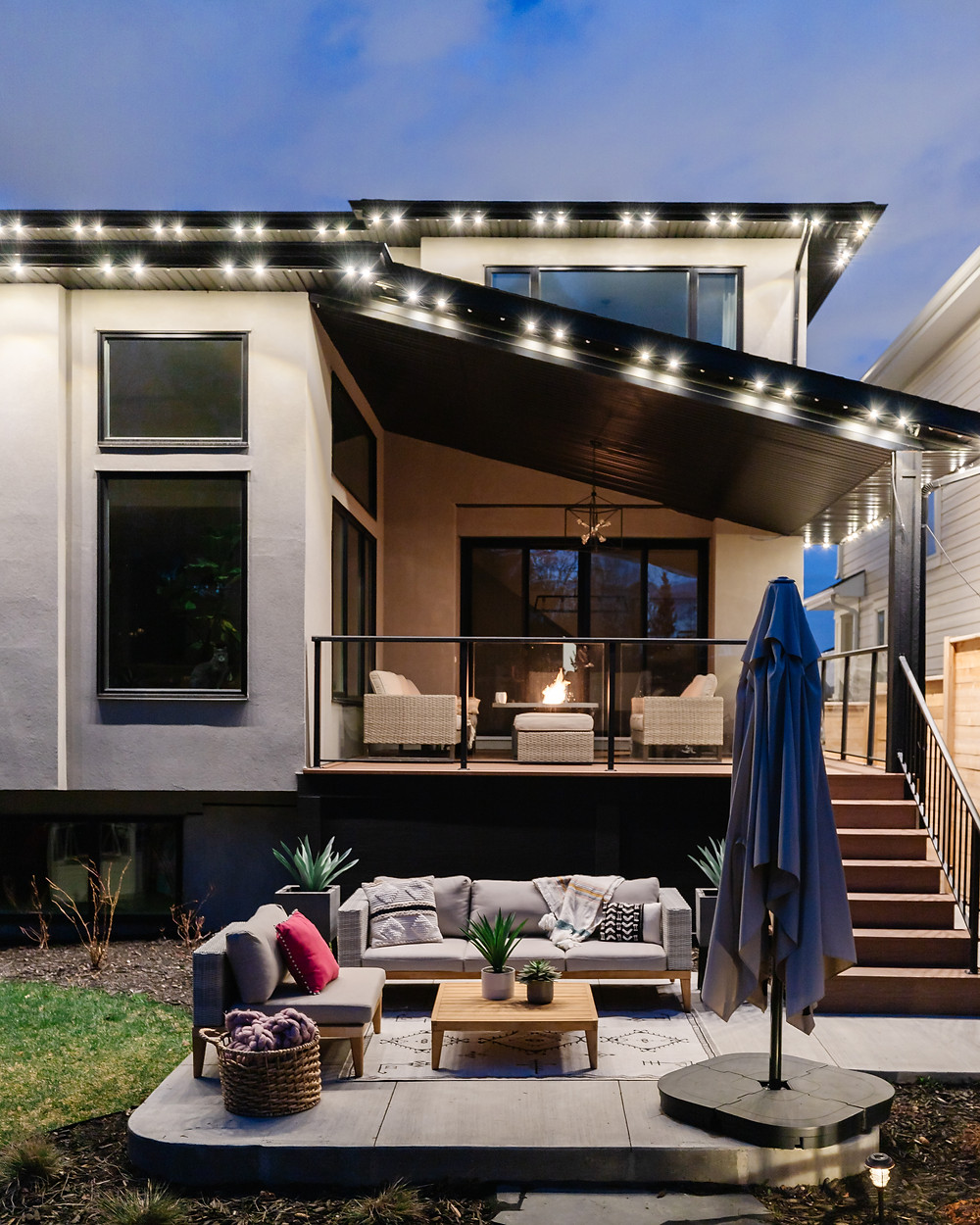 A modern home exterior with warm white Gemstone Lights shining down on a beautiful styled patio with a fire table, white sofa set succulents, a wooden table, and a large patio umbrella.
