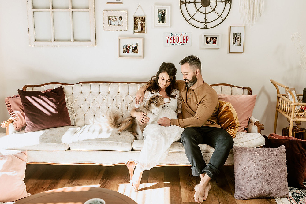 A pregnant mom in a vintage looking white dress sits in a boho wicker rattan high back chair surrounded by flowers and pampas grasses as she rests her hands on her pregnant stomach at her boho inspired baby shower.