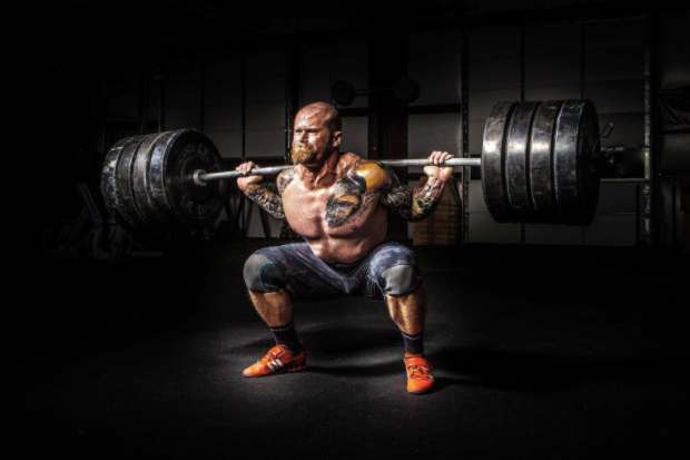 A man working out, and lifting a large amount of weight