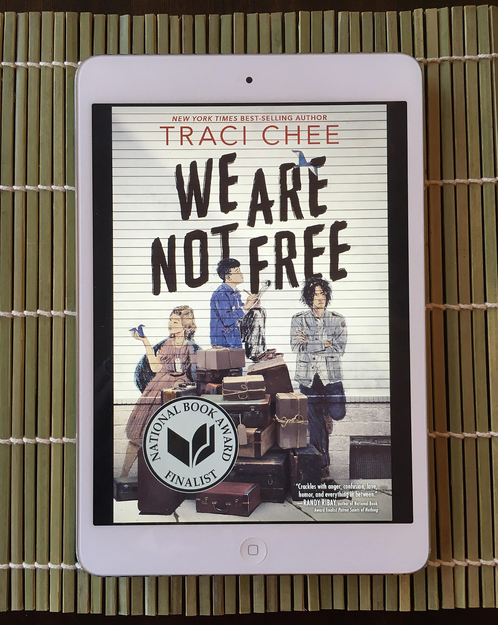 "Cover photo of the book ""We Are Not Free"" by Traci Chee as displayed on a kindle, as pictured laying on a sushi mat."