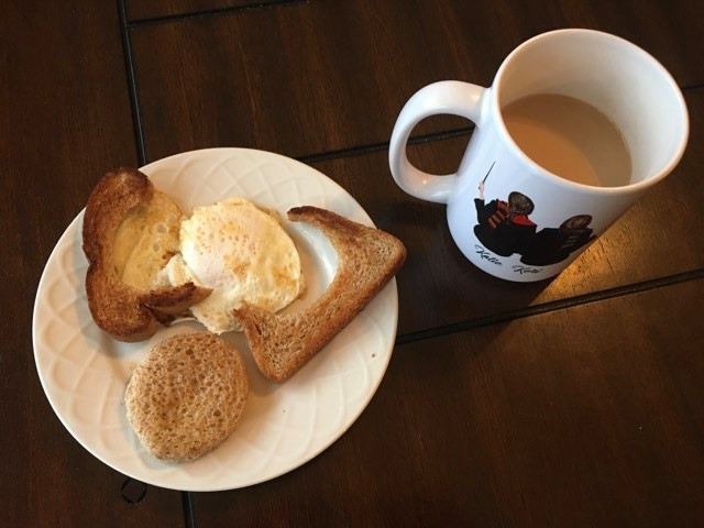 A plate with a sunny-side-down egg and a broken, wonky piece of toast that was supposed to be the basket for an egg-in-a-basket.
