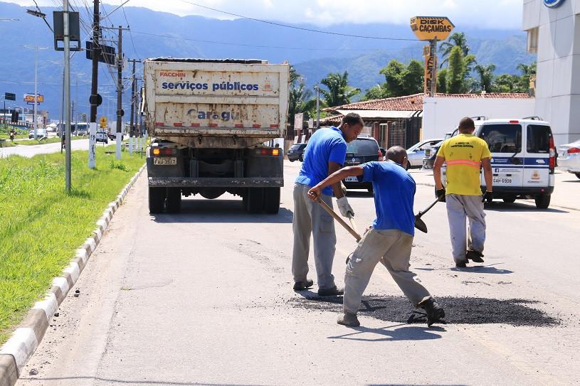 Homens espalham material asfáltico com pás, em pista marginal à rodovia SP-55, tendo um caminhão da Sesep ao fundo (Foto: Luís Gava/PMC)