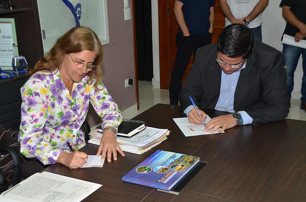 Prefeito Aguilar Junior e a procuradora do estado Maria Cristina dos Santos Martins Toledo estão sentados à mesa. Ambos assinam documentos. - Foto: Divulgação/PMC