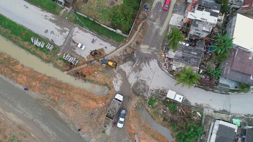 Imagem aérea de uma retroescavadeira, ao lado de dois caminhões, trabalha na instalação de tubos de concreto ligando uma vala a um canal (Foto: Cláudio Gomes/PMC)