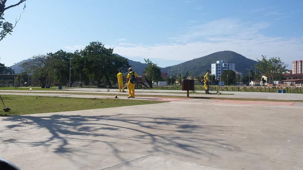 Três funcionários com roçadeira e vassoras fazem a limpeza do Parcão - Foto: Divulgação/PMC