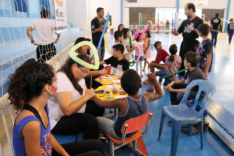 Monitoras pintam o corpo de crianças e outras brincam com bexigas coloridas enquanto aguardam para serem pintadas também. - Foto: Claudio Gomes/PMC