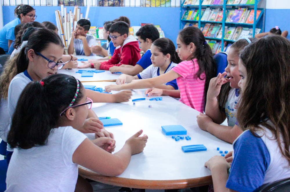 Sala de aula em uma mesa oval, 14 alunos, entre meninos e meninas fazem atividades com jogos acompanhados de uma professora. - Foto: Janaína Castro/PMC