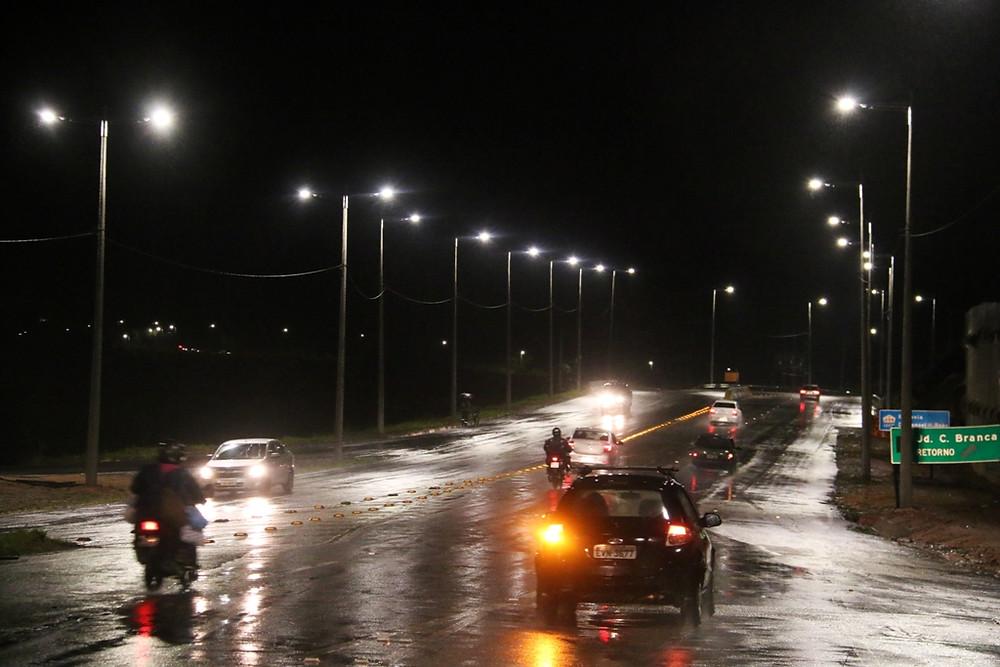 Vista noturna de veículos que sobem a serrinha já iluminada. Com a chuva, a pista molhada reflete a iluminação - Foto: Luiz Gava/PMC