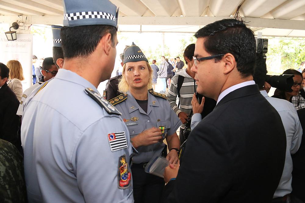 A Coronel Eliane Nikoluk conversa com o prefeito Aguilar Junior, que está ao lado de mais dois integrantes da Polícia Militar, todos em pé (Foto: Luís Gava-PMC)