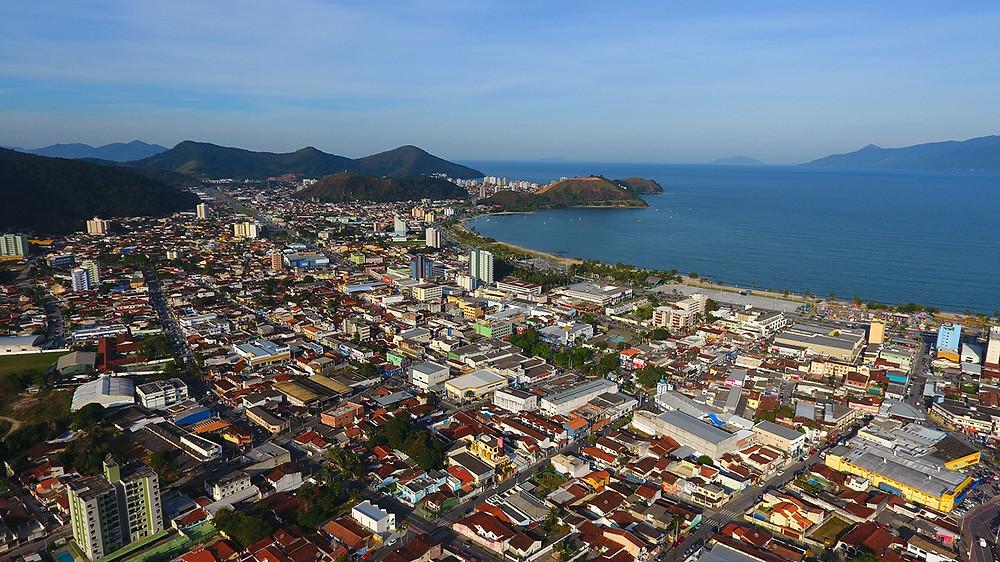 Foto aérea de Caraguatatuba, mostrando prédios da região central e ao longe o morro do camaroeiro, o mar e o céu azul (Foto: Luís Gava e Cláudio Gomes-PMC)
