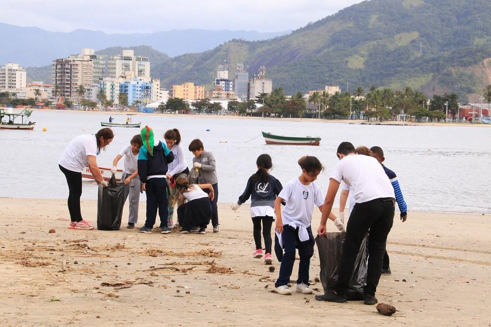 Participantes da ação de limpeza na Praia do Camaroeiro recolhendo o lixo deixado na praia (Luis Gava/PMC)