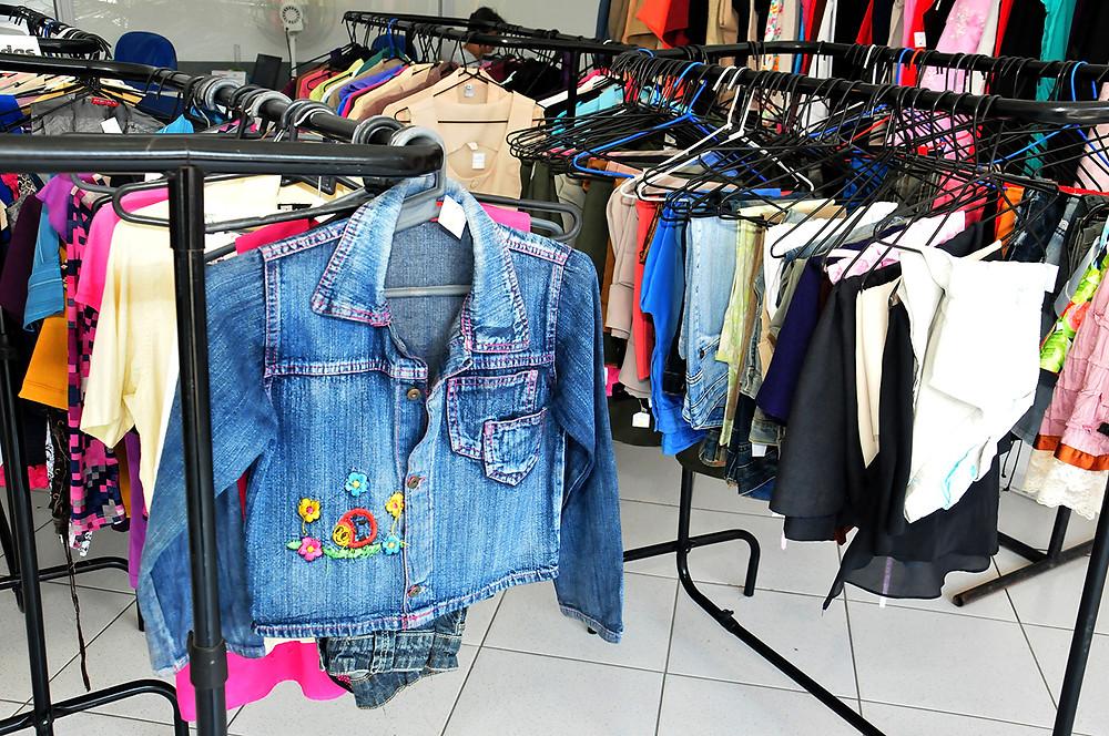 #PraCegoVer arara de roupas com blusa e jaquetas expostas na Sede do Fundo Social (Foto: Luis Gava/PMC)