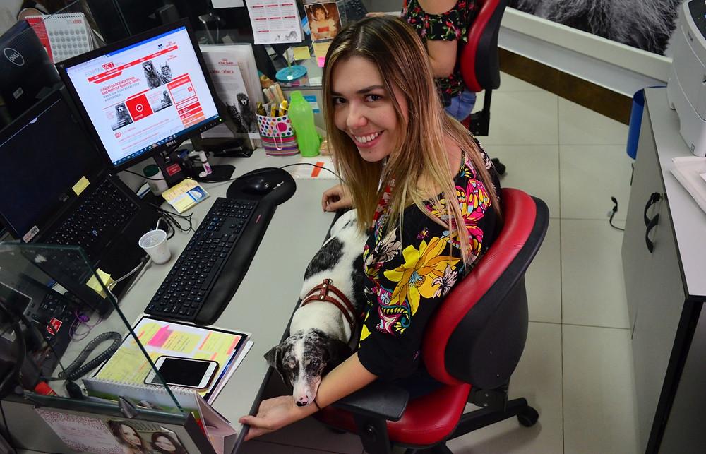 A atendente do SAC Maiara Vieira trabalha com a sua cachorrinha no colo. Política pet friendly contou na hora de trocar de emprego (Foto: Fabiana Assis/G1)