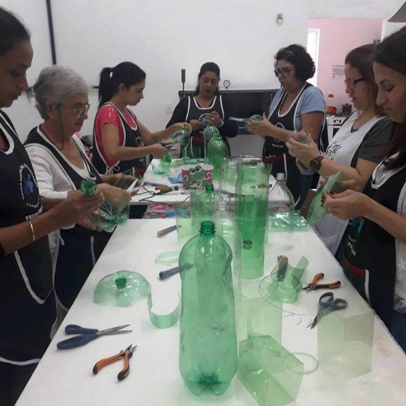 Voluntárias manuseando garrafas PET para montagem da árvore. - Foto: Divulgação/PMC