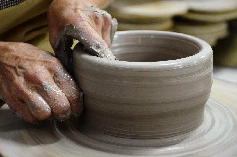 Mão de pessoa moldando uma tigela de argila. - Foto: JC Curtis/Fundacc