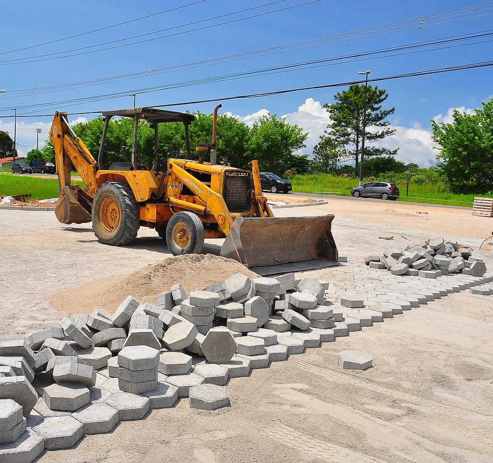 Retroescavadeira em rua parcialmente pavimentada por bloquetes. Na frente da máquina e bloquetes empilhados. (Foto: Cláudio Gomes/PMC)