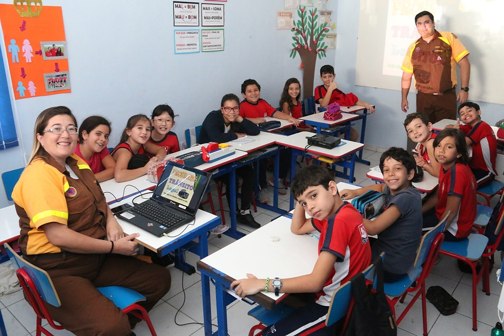 Alunos sentados e dois agentes de trânsito, instrutores do programa, posam para foto na sala de aula - Foto: Luis Gava/PMC