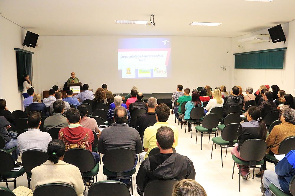 Pessoas sentadas em cadeiras dispostas em uma sala com uma projeção na parede, ouvem a fala do presidente da Associação Comercial de Caraguatatuba (Foto: Luís Gava/PMC)