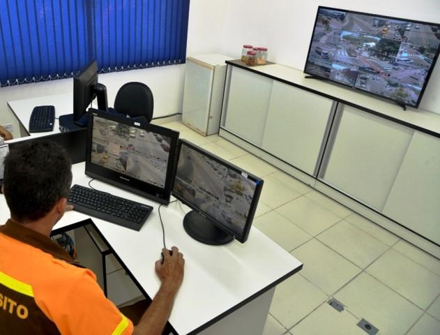 Sala de monitoramento com um funcionário trabalhando em um computador e tendo a frente um monitor maior com várias imagens de pontos da cidade, monitorados por câmeras de segurança (Foto: Claudio Gomes/PMC)