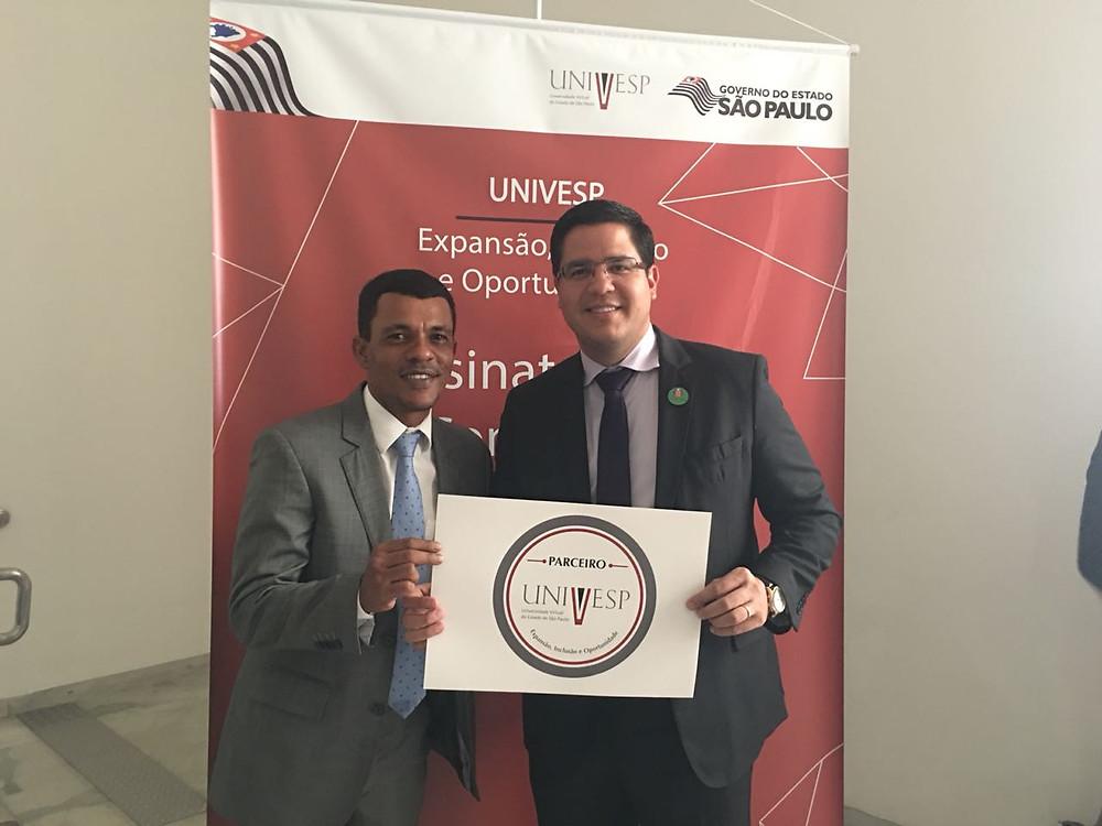 Prefeito Aguilar Junior e Vereador Duda Silva seguram placa de parceria da Univesp - Foto: Divulgação/PMC