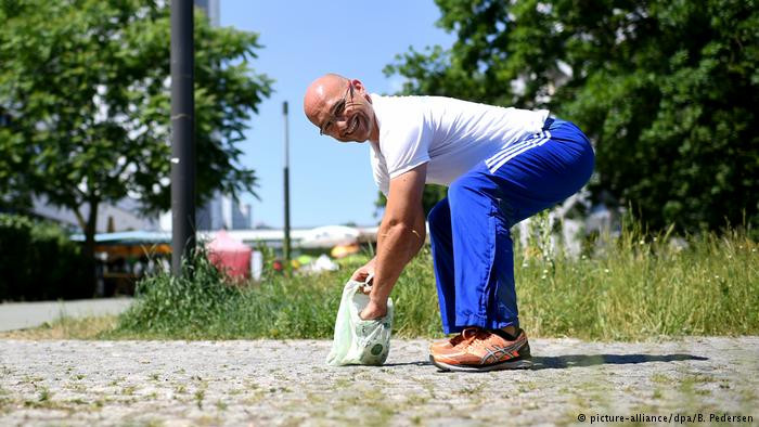 Cientista esportivo Julian Grzybowski mostra como se abaixar corretamente para recolher lixo do chão