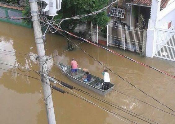 Moradores percorrem rua alagada em bote a remo