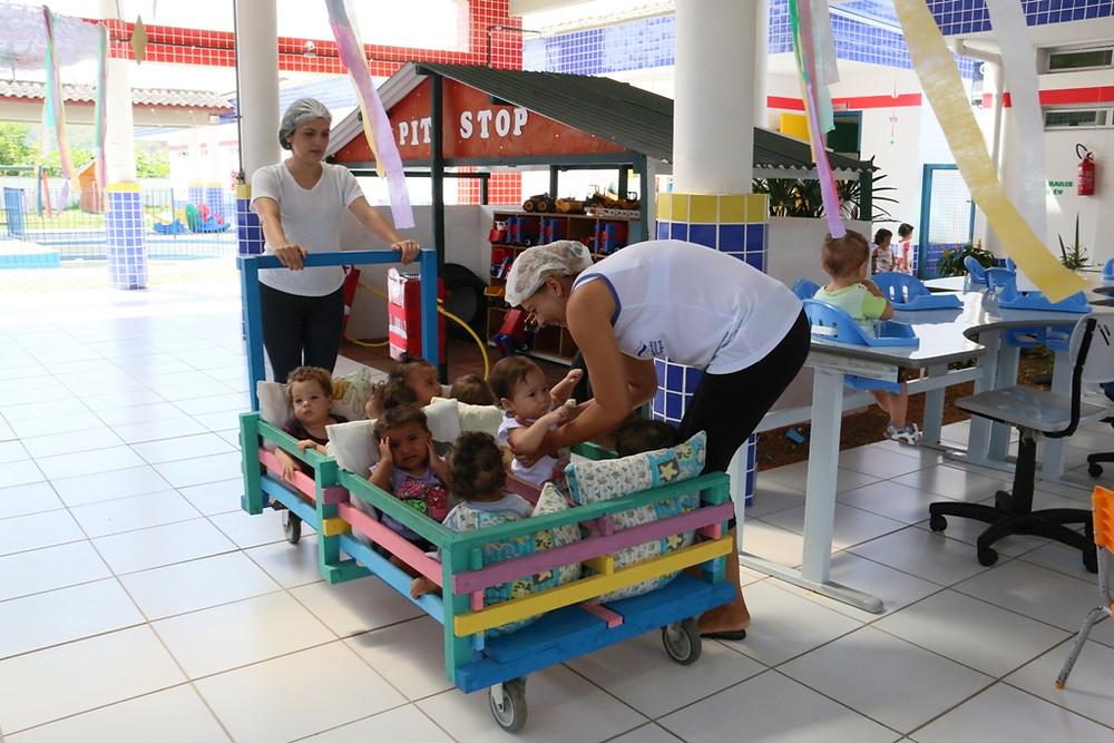 Duas agentes de desenvolvimento infantil (ADIs) passeiam com oito bebês em um carrinho de madeira pelo pátio da unidade escolar - Foto: Divulgação/PMC