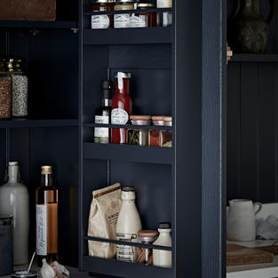 Make every inch count with a concealed larder set over deep drawer units. Opt for a fully coordinated painted finish, across the tongue and groove panelling right through to the door hung spice racks, and this daily storage is elevated to a feature piece.
