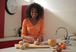 Canva - Cheerful woman cutting potatoes