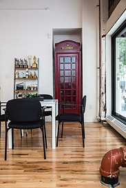Workroom with chairs, a desk, and a red telephone box.