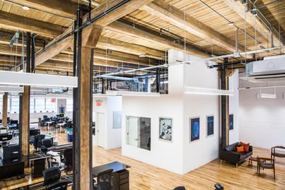 Open office layout with exposed wood ceiling.